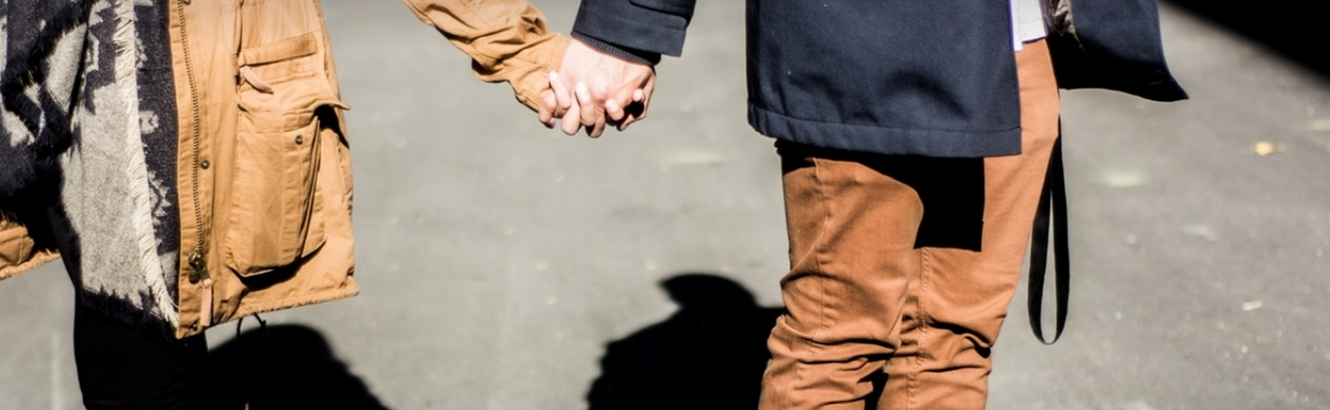 Couple holding hands on the street.