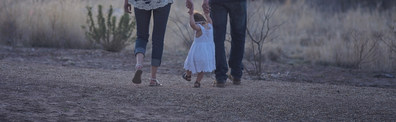 Toddler walking with her parents and holding hands.
