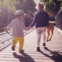 Kids holding hands and running across a bridge.