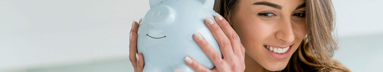 Young woman shaking piggy bank.