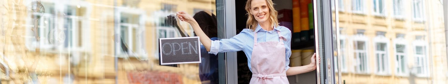 Woman hanging an Open sign on her business