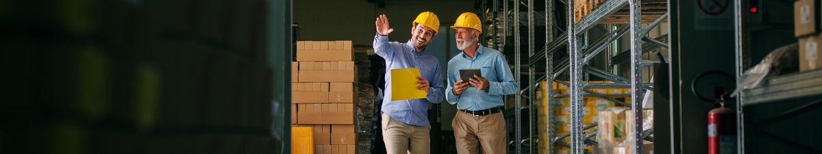 Two contractors talking in a warehouse